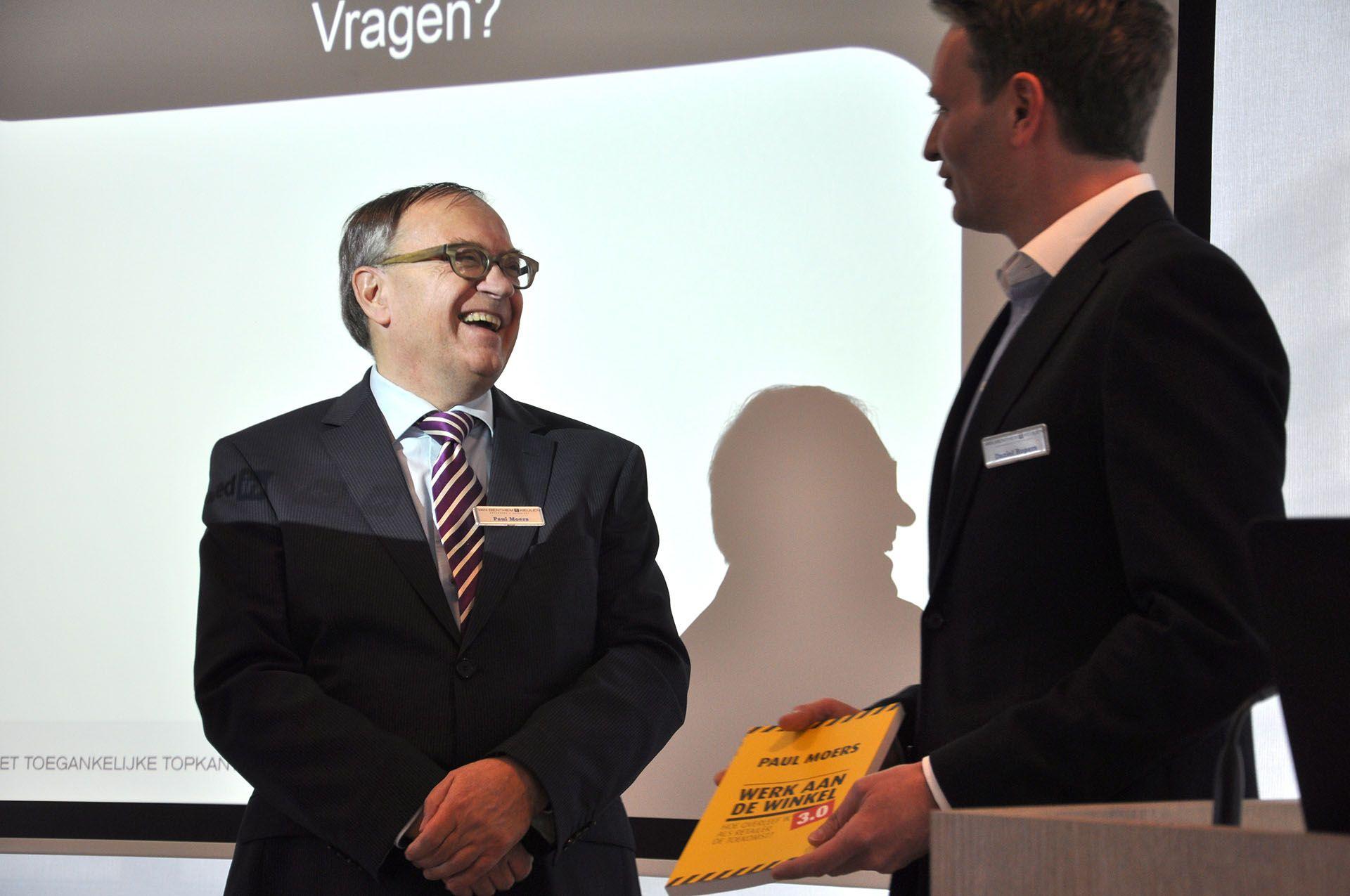 Paul Moers overhandigt boek aan Daniel Ropers van Bol.com bij van Benthem en Keulen in Utrecht